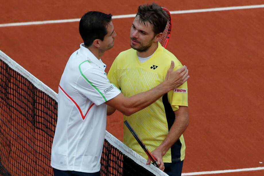 Guillermo Garcia-Lopez, left, consoles Stan Wawrinka after ousting the Australian Open champion in the first round of the French Open. Photo: Michel Euler, STF / AP