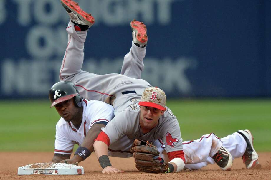 Red Sox second baseman Dustin Pedroia lands on the Braves' Justin Upton during a double play. Photo: Brant Sanderlin / Atlanta Journal-Constitution / Atlanta Journal-Constitution