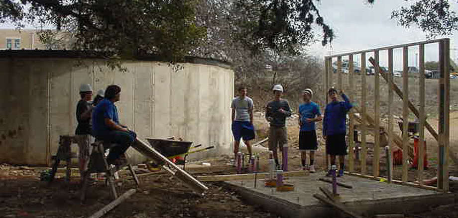 Under the direction of retiring Bandera High School teacher Brad Flink, students construct a stormwater catch system to funnel runoff from the school's parking lot into what are now two 42,000-gallon tanks. Photo: Courtesy Photo