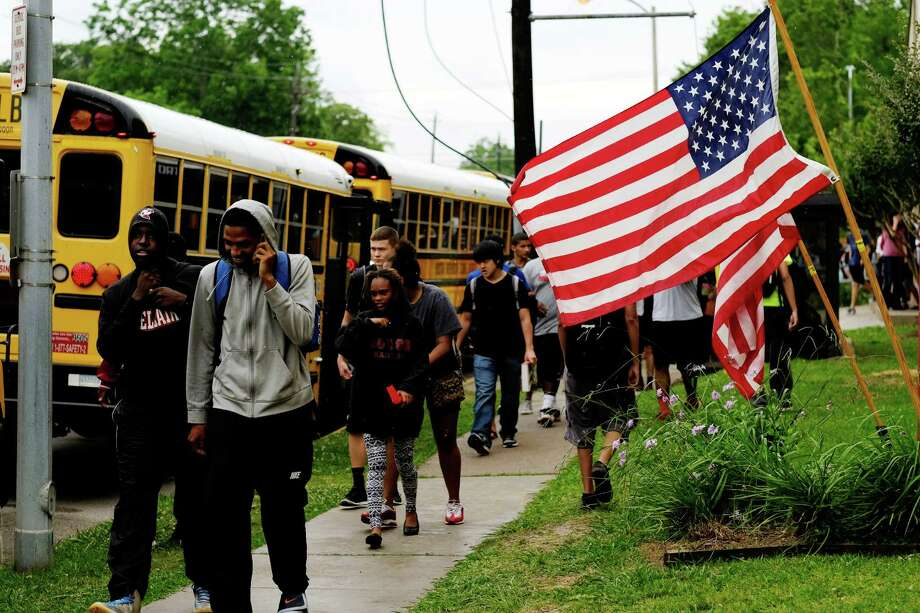 With American flags in the background, students make their way to their respective buses after the final bell, Monday, May 26, 2014, at Bellaire Senior High School in Bellaire, Texas. HISD held one of its makeup days this Memorial Day holiday. © TODD SPOTH Photo: TODD SPOTH, © TODD SPOTH / © TODD SPOTH