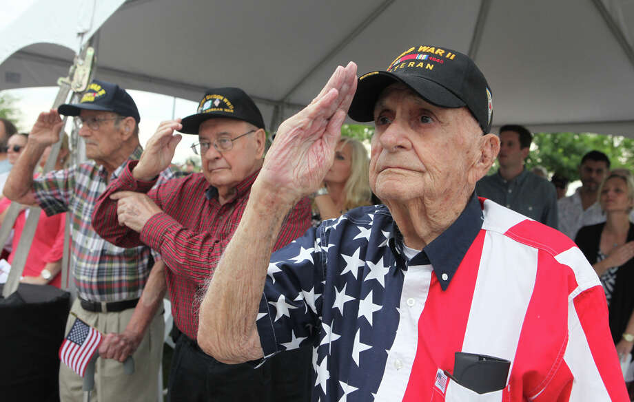 World War II veteran William Jackson,left,  Korean War veteran Joe Romano, center, and WWII veteran Aron Seibel, right, salute during the Presentation of Colors during Sugar Land's 6th Annual Memorial Day Ceremony in Sugar Land, Texas on Monday, May 26, 2014. (AP Photo/The Courier, Alan Warren) Photo: Alan Warren, Associated Press / AP