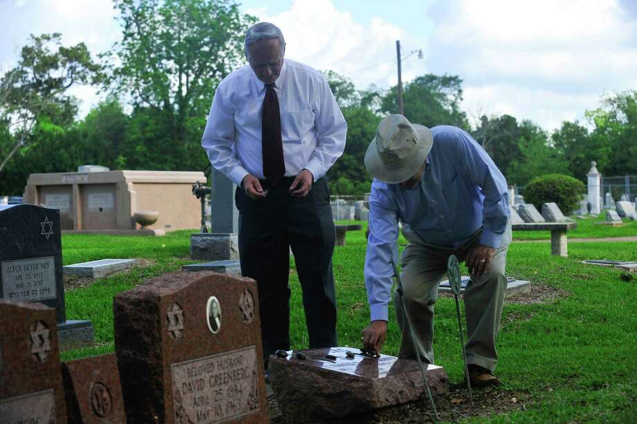 Alan Sampson, left, and Ralph Night place stones on the graves of the Greenberg brothers in Hebrew Rest Cemetery on Tuesday. Photo provided by Jon Shapley Photo: Jon Shapley