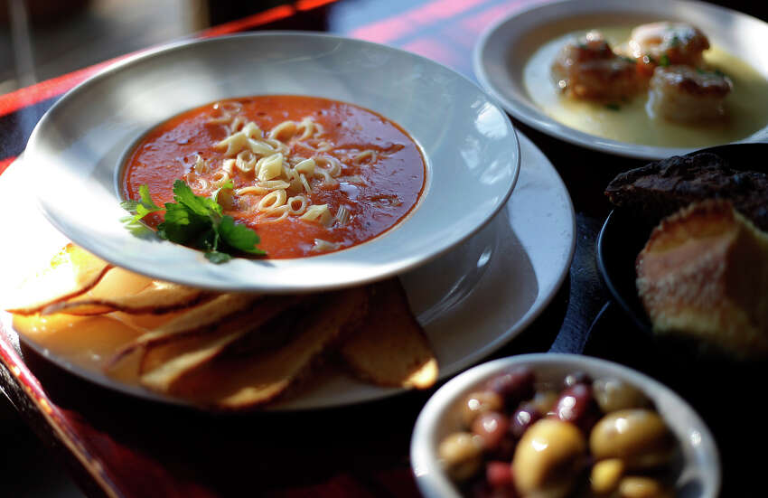 Pasta e fagioli soup surrounded by olives, bread and Paesano's signature dish, shrimp Paesano