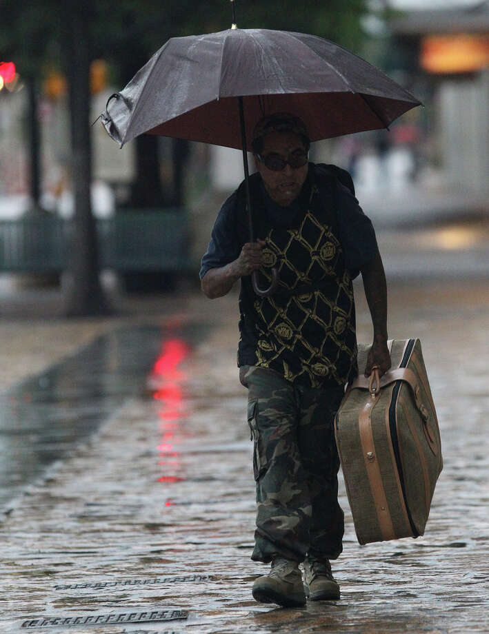 Eddie Garcia walks through drizzle on Alamo street Tuesday May 27, 2014. Flash flooding is still possible in the San Antonio area. Photo: JOHN DAVENPORT, San Antonio Express-News / ©San Antonio Express-News/John Davenport
