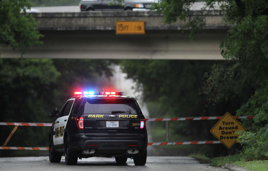 A San Antonio Park police officer guards the entrance to Olmos basin Tuesday May 27, 2014 after rainfall has been present in the area recently. Flash flooding is still possible in the San Antonio area. Photo: JOHN DAVENPORT, San Antonio Express-News / ©San Antonio Express-News