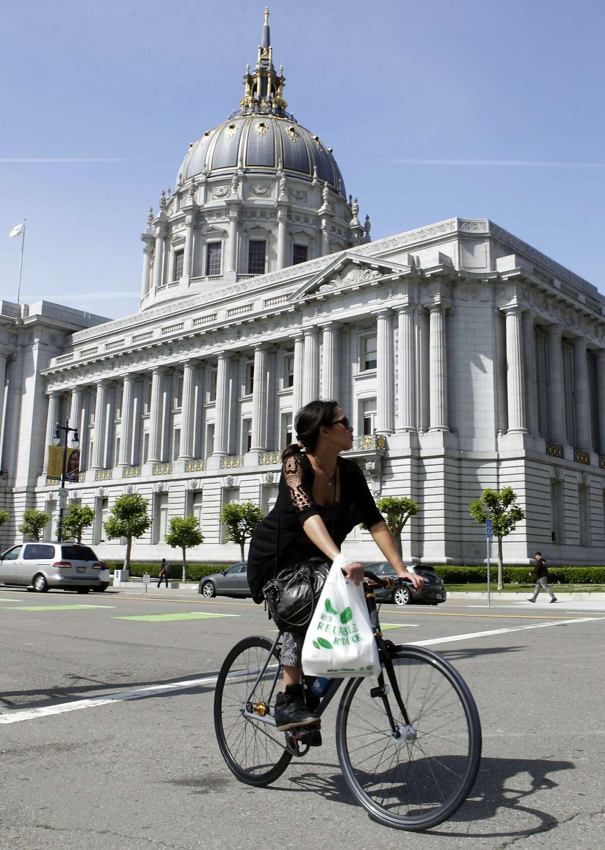 A bicyclist cruises past City Hall in San Francisco.