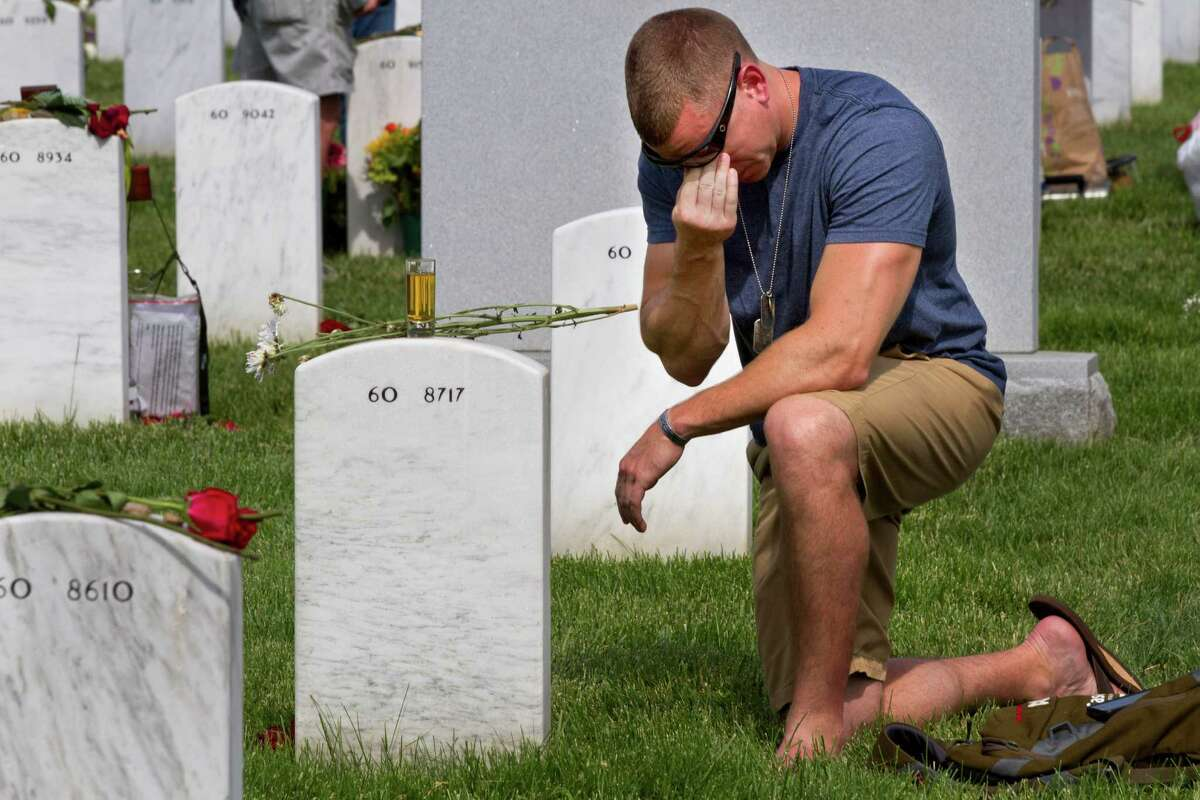 Former Army Sgt. Anthony Brown, 31, of Arlington, Va., wipes away tears as he visits his best friend, Army Sgt. Scott Kirkpatrick, on Memorial Day at Arlington National Cemetery in Arlington, Va., Monday, May 26, 2014. Kirkpatrick died serving in Iraq in 2007 at the age of 27, and is buried in Section 60, where many of the soldiers who died in Iraq and Afghanistan are buried, (AP Photo/Jacquelyn Martin) ORG XMIT: VAJM203