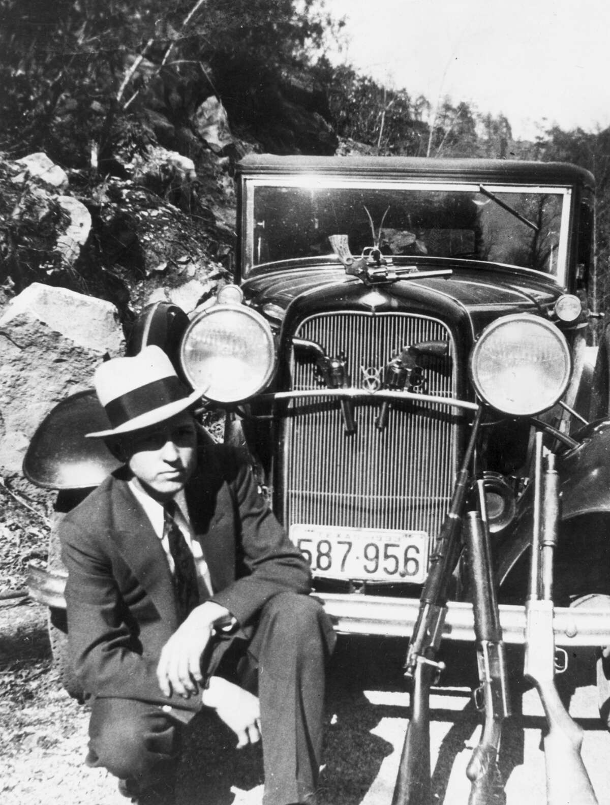 Clyde Barrow crouches in front of a car with a handgun hanging from the hood ornament, two handguns in the front grill and three rifles laid against the front fender, possibly in Joplin, Mo., in April 1933.