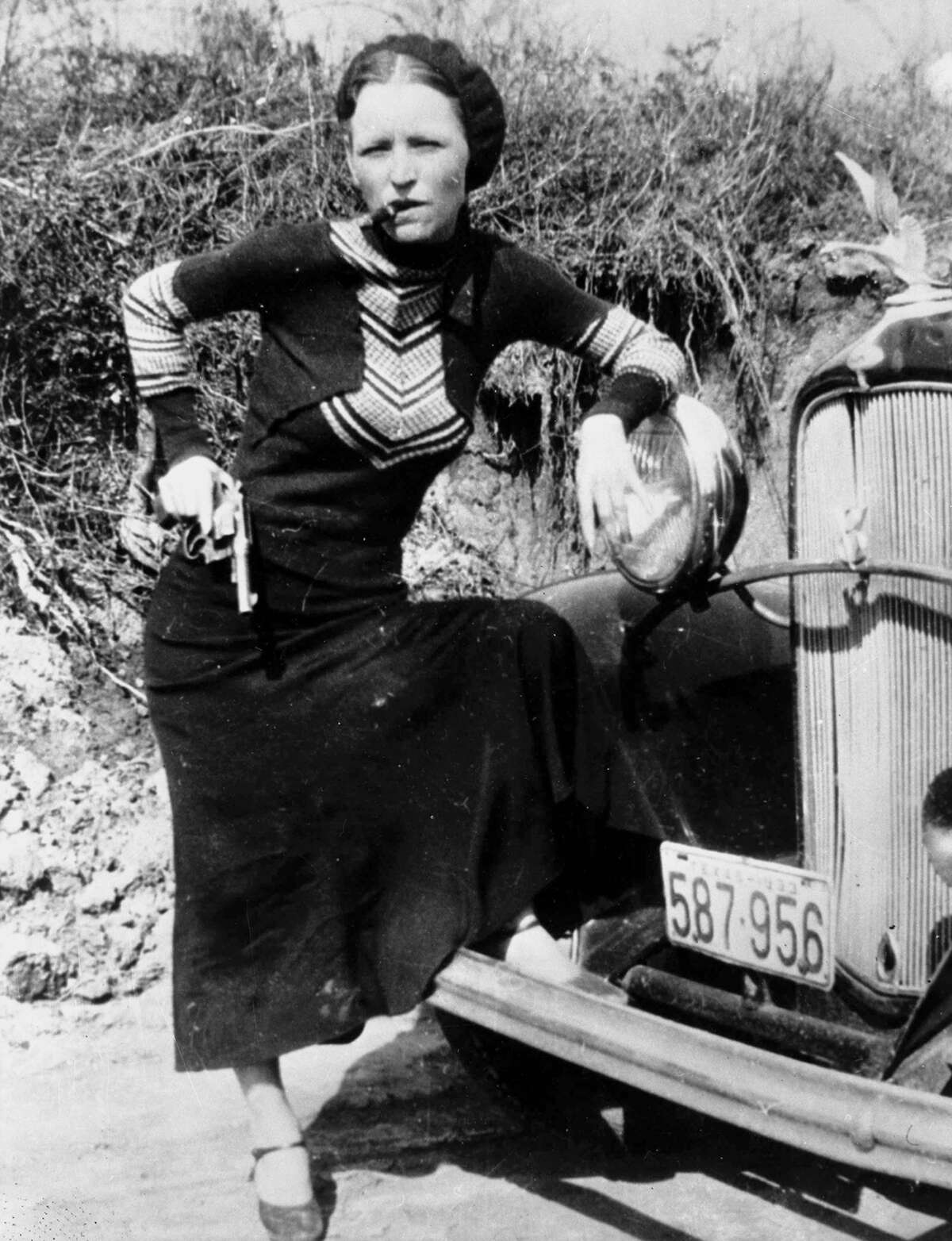 Bonnie Parker poses with a cigar and gun in a photo made infamous by the press, circa 1932.