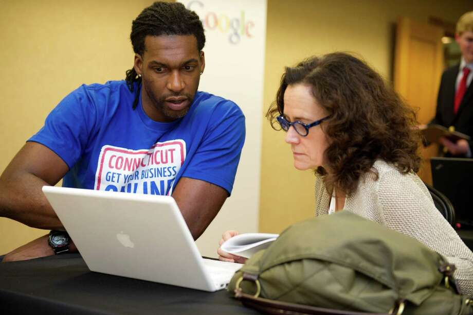 Marvin Augustin, left, helps Christian Science Practitioner and teacher Giulia Nesi with her website, open2spirituality.com, during the Google program Connecticut Get Your Business Online at Dolce in Norwalk, Conn., on Tuesday, May 27, 2014. Photo: Lindsay Perry / Stamford Advocate