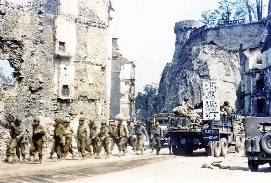 Operation Overlord Normandy, United States Army trucks and jeeps are driving through the ruins of Saint-Lo. July 1944. A group of American soldiers is walking along the street. The town was almost totally destroyed by 2,000 Allied bombers when they attacked German troops stationed there during Operation Overlord in June. France. Photo: Galerie Bilderwelt, Getty Images / 2010 Galerie Bilderwelt