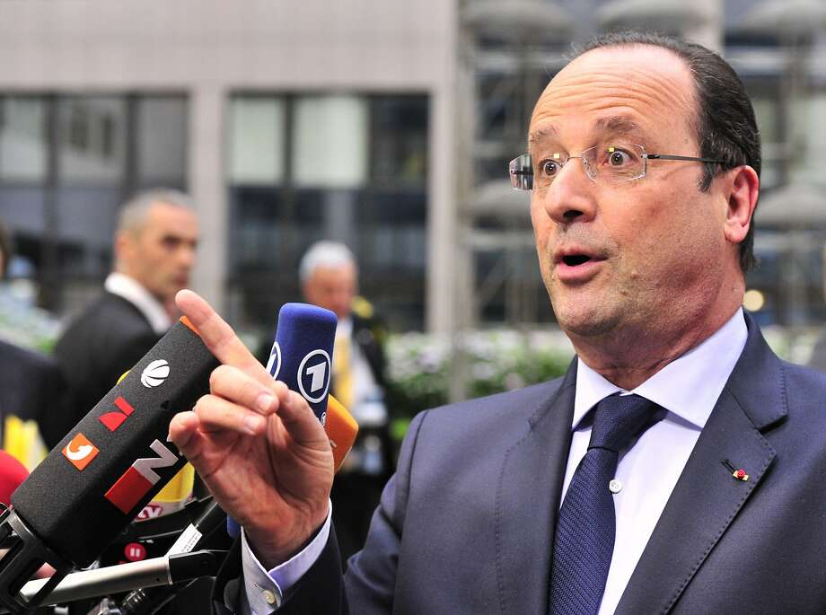 French President Francois Hollande answers journalists' questions as he arrives at EU headquarters in Brussels to take stock of recent elections. Photo: Georges Gobet, AFP/Getty Images