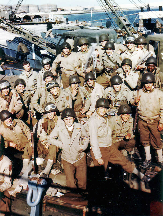 American assault troops in Normandy on the dawn of the invasion. All these men wear battle dress with wool trousers and jacket M1941 combat or tanker jacket. Behind these men are visible cranes dock that used to engineering skidding supplies on the beaches at the end of the assault. At right stands a black soldier dressed in fatigues, which probably belongs to the 320th Barrage Balloon Battalion or one of the support elements of the 5th Brigade amphibious engineering. Photo: Galerie Bilderwelt, Getty Images / Conseil Régional de Basse-Normandie / National Archives USA