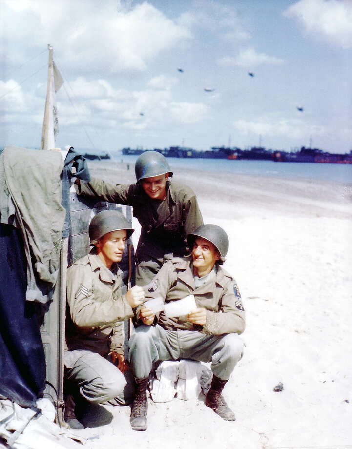 Operation Overlord Normandy, Three American soldiers from the 1st Engineer Special Brigade are looking at photos from home. June 1944. Landing Ships Tank (LST) and other vessels are on the beach at Omaha and barrage balloons are up in the air for protection. France. Photo: Galerie Bilderwelt, Getty Images / 2010 Galerie Bilderwelt