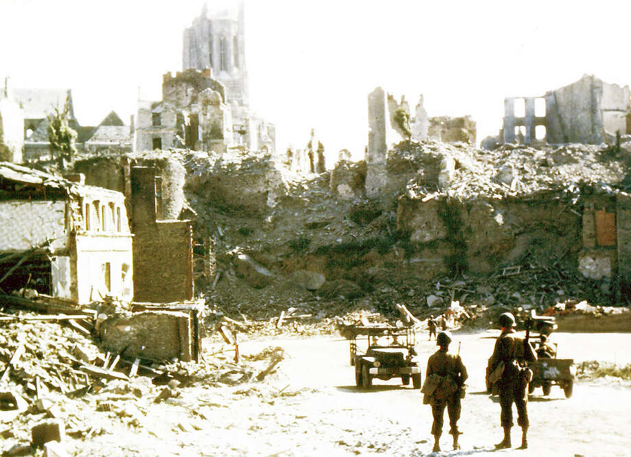 Operation Overlord Normandy, Two American soldiers are watching two United States Army jeeps driving through the ruins of the center of Saint-Lo. August 1944. The town was almost totally destroyed by 2,000 Allied bombers when they attacked German troops stationed there during Operation Overlord in June. France. Photo: Galerie Bilderwelt, Getty Images / 2010 Galerie Bilderwelt