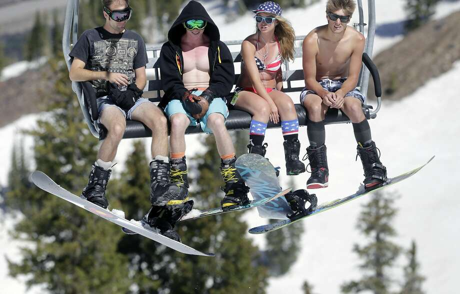 Dressed more for the beach than the slopes, skiers ride the lift on the final day of skiing at Snowbird outside of Salt Lake City. Photo: Rick Bowmer, Associated Press