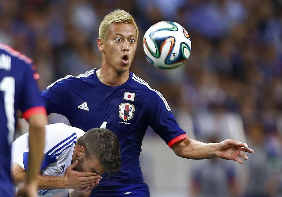 Holy moley, that hit your face hard:Keisuke Honda battlesGiorgos Merkis for the ball during afriendlysoccer match between Japan and Cyprus. (Saitama,   Japan.) Photo: Shizuo Kambayashi, Associated Press