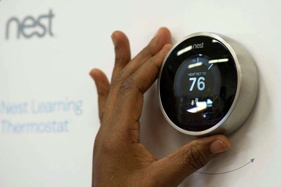 A customer checks a Nest Labs Inc. digital thermostat on display at a Home Depot Inc. store in Emeryville, California, U.S., on Tuesday, Jan. 14, 2014. Google Inc., after struggling to catch Apple Inc. in consumer gadgets, is buying Nest Labs Inc., the digital thermostat maker for $3.2 billion in cash. Photographer: David Paul Morris/Bloomberg Photo: David Paul Morris / © 2014 Bloomberg Finance LP