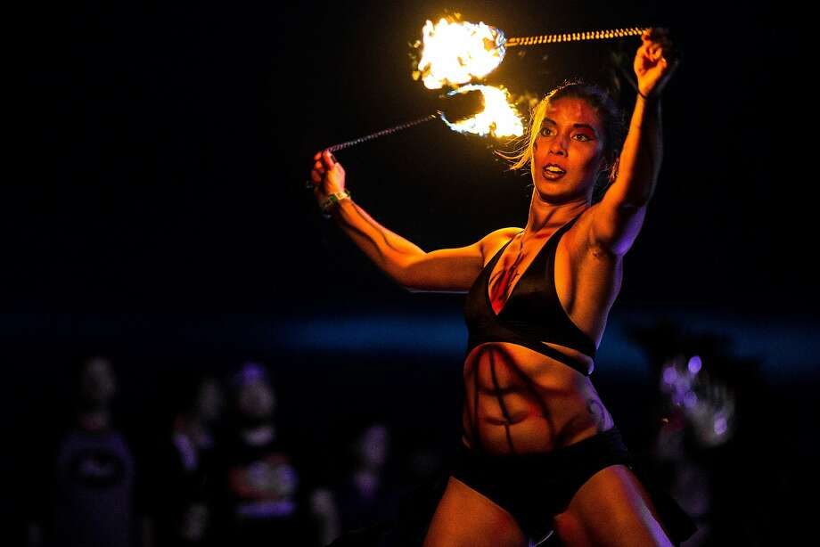 "A fire dancer of the ""soul metal"" band Super Geek League spins torches during the Sasquatch music 