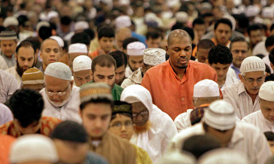 A man of faith, Hakeem prays among a crowd during the Muslim holiday that signals the end of the month of fasting known as Ramadan. Photo: Melissa Phillip, Chronicle / © 2012 Houston Chronicle