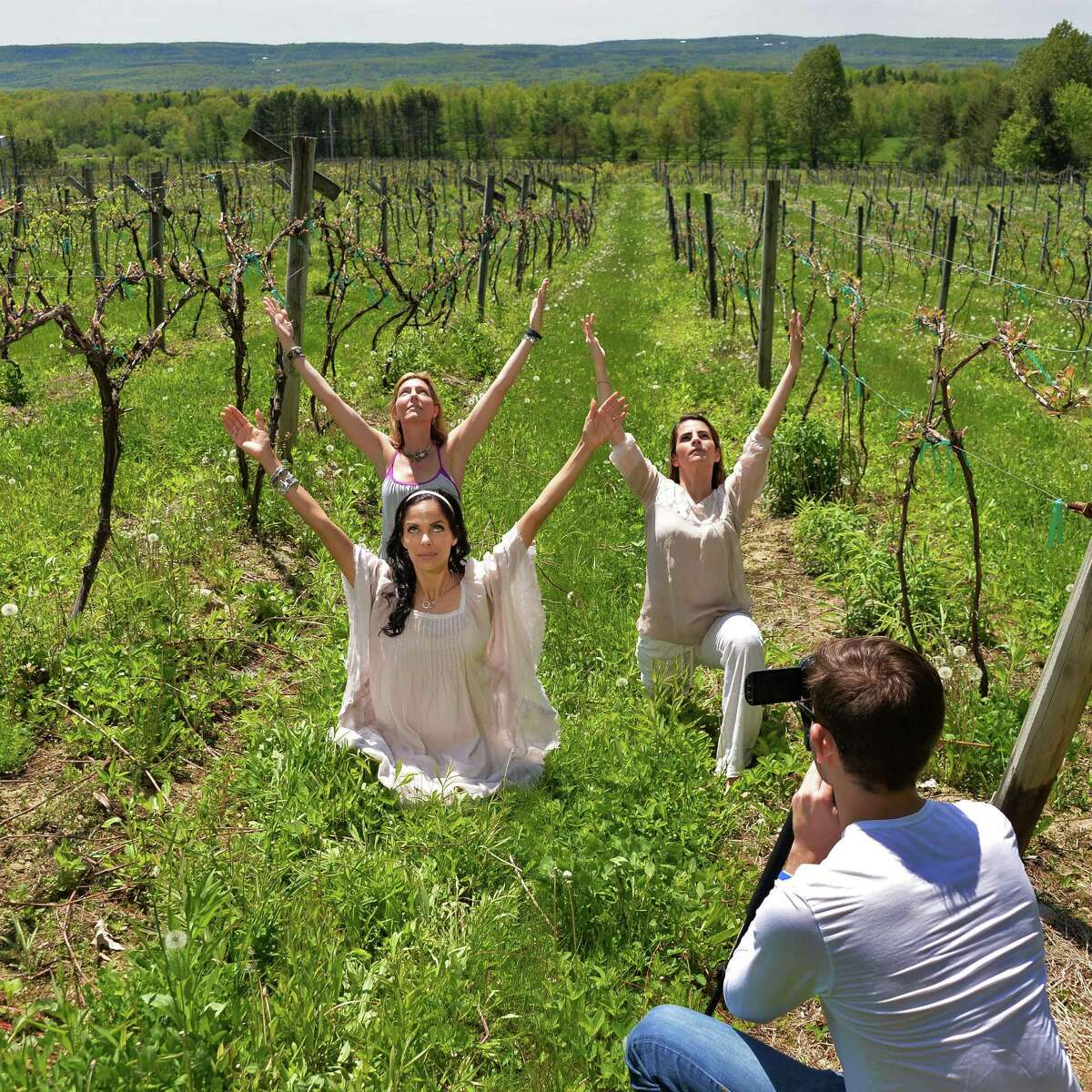 From left, Lisa O'Brien of Lifeyum, Franca DiCrescenzo of Armida Rose Realty and Gina Tralongo of Freestyle Fitness & Yoga strike yoga poses for videographer Kaleb Dubin as they shoot a promotional video for the upcoming Vinyoga Festival at the Altamont Vineyard Winery Wednesday May 21, 2014, in Altamont, NY. (John Carl D'Annibale / Times Union)