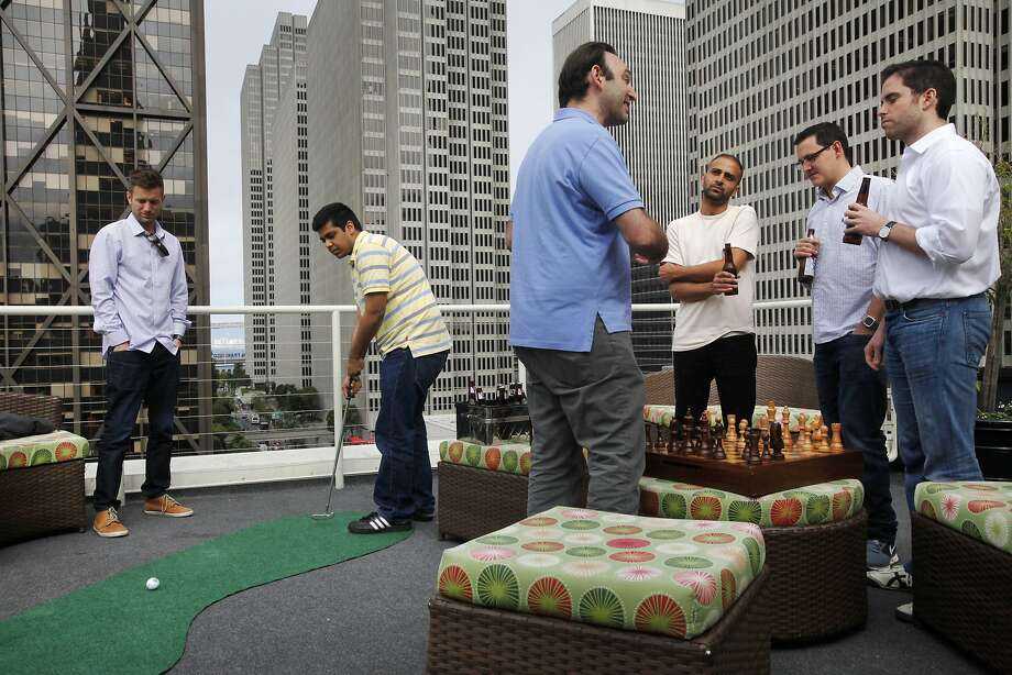 Skillz employees Jared Ricardo (left) and Prasheel Vissapragada practice putting as Anthony Jacobson, Shady Alzayat (host of the co-working space), Simon Rider and Skillz co-founder Casey Chafkin chat on the rooftop lounge. Photo: Leah Millis, The Chronicle