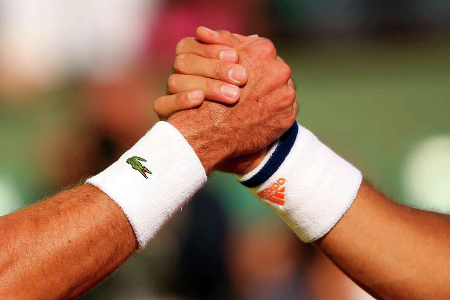 Jo-Wilfried Tsonga of France shakes hands at the net with Edouard Roger-Vasselin of France after their men's singles match on day one of the French Open at Roland Garros on May 25, 2014 in Paris, France. Photo: Clive Brunskill, Getty Images / 2014 Getty Images