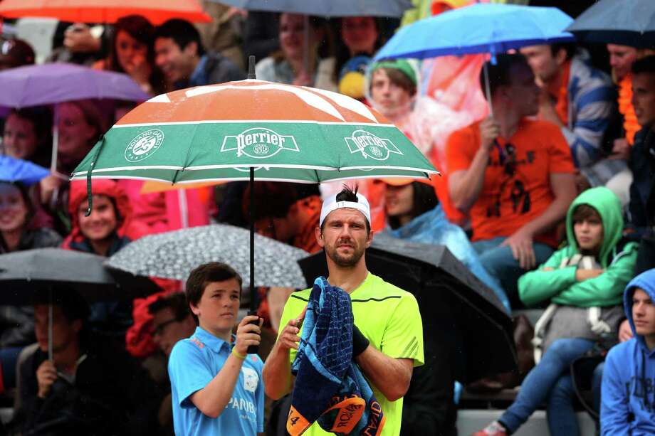 Jurgen Melzer of Austria waits for play to start as he shelters from the rain under an unbrealla during his men's singles match against David Goffin of Belgium on day two of the French Open at Roland Garros on May 26, 2014 in Paris, France. Photo: Matthew Stockman, Getty Images / 2014 Getty Images