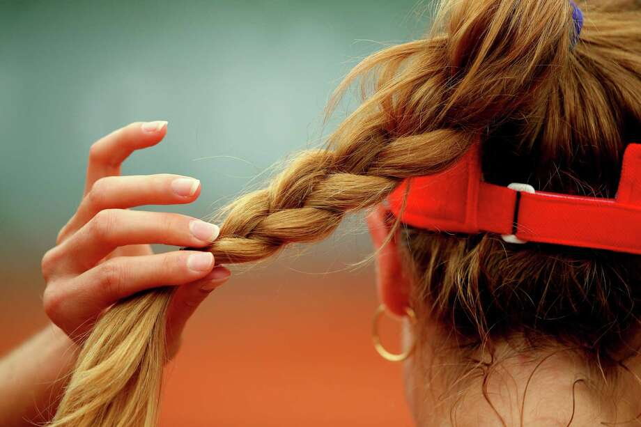 Alize Cornet of France adjusts her hair during a break in her women's singles match against Ashleigh Barty of Australia on day two of the French Open at Roland Garros on May 26, 2014 in Paris, France. Photo: Clive Brunskill, Getty Images / 2014 Getty Images
