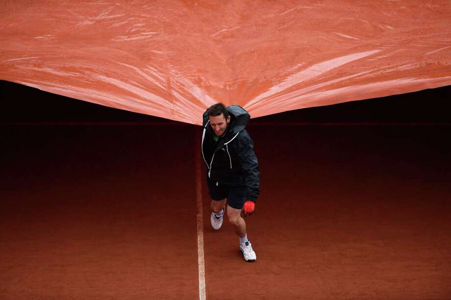 A groundsman pulls the rain cover across Court Suzanne Lenglen as rain interrupts play on day two of the French Open at Roland Garros on May 26, 2014 in Paris, France. Photo: Matthias Hangst, Getty Images / 2014 Getty Images
