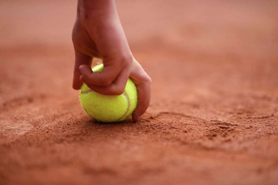 A ballboy holds a tennis ball during a match on day three of the French Open at Roland Garros on May 27, 2014 in Paris, France. Photo: Matthias Hangst, Getty Images / 2014 Getty Images