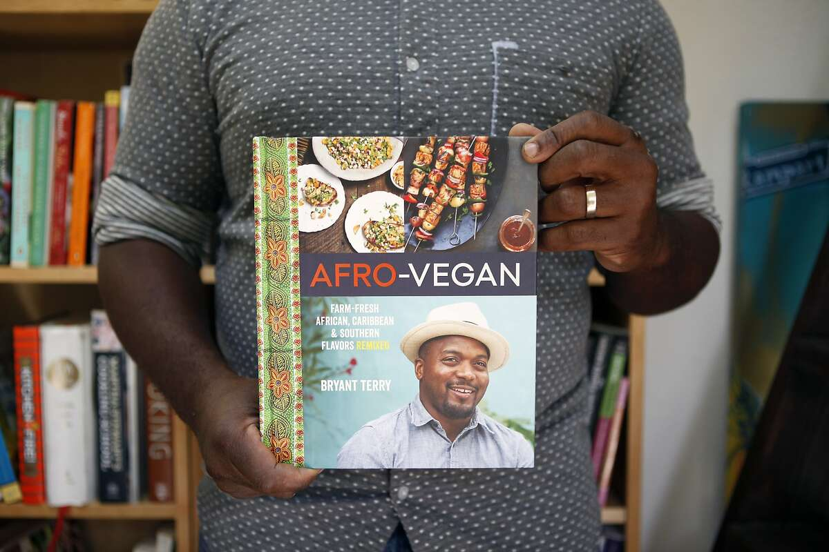 Chef, author and food activist Bryant Terry holds a copy of his new cookbook,