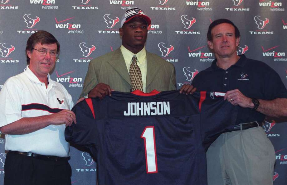 Houston Texans general manager Charley Casserly, left, and head coach Dom Capers, right, welcome their first pick in the NFL draft Andre Johnson, a wide receiver from the University of Miami, Saturday night, April 26, 2003, at Reliant Stadium in Houston. Photo: Kevin Fujii, Houston Chronicle