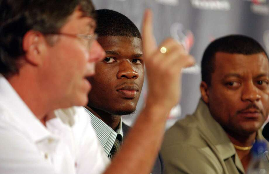Andre Johnson, the  Miami wide receiver who was the third selection in the first round of the 2003 NFL Draft. listens to general manager Charley Casserly during the press conference, after being signed by  the Houston Texans, Tuesday afternoon. Johnson's advisor, Andre Melton, is on the far right. Photo: Karen Warren, Houston Chronicle / Houston Chronicle