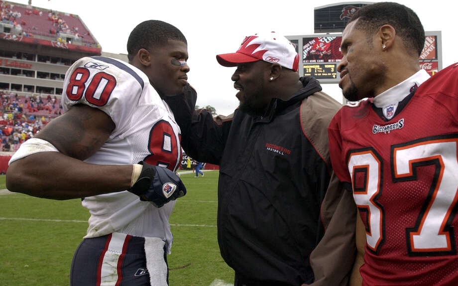 Texans wide receiver Andre Johnson is greeted after the game Sunday by Tampa Bay standout Warren Sap and reciever Keenan McCardell after the Texans loss to the Bucs 16-3 on Dec. 14, 2003. Photo: Karl Stolleis, Houston Chronicle