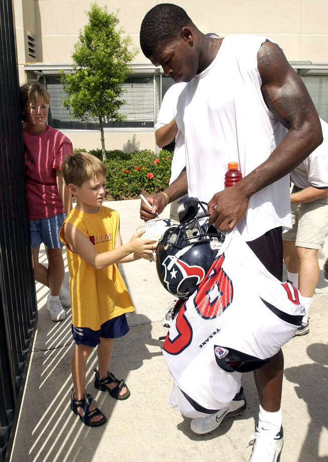 Houston Texan Andre Johnson (80) signs an autograph for Brennan Gallent, 7, of Louisiana, after practice on the first day of training camp, Saturday, July 26, 2003 in Houston. Photo: CHRISTOBAL PEREZ, HOUSTON CHRONICLE / HOUSTON CHRONICLE