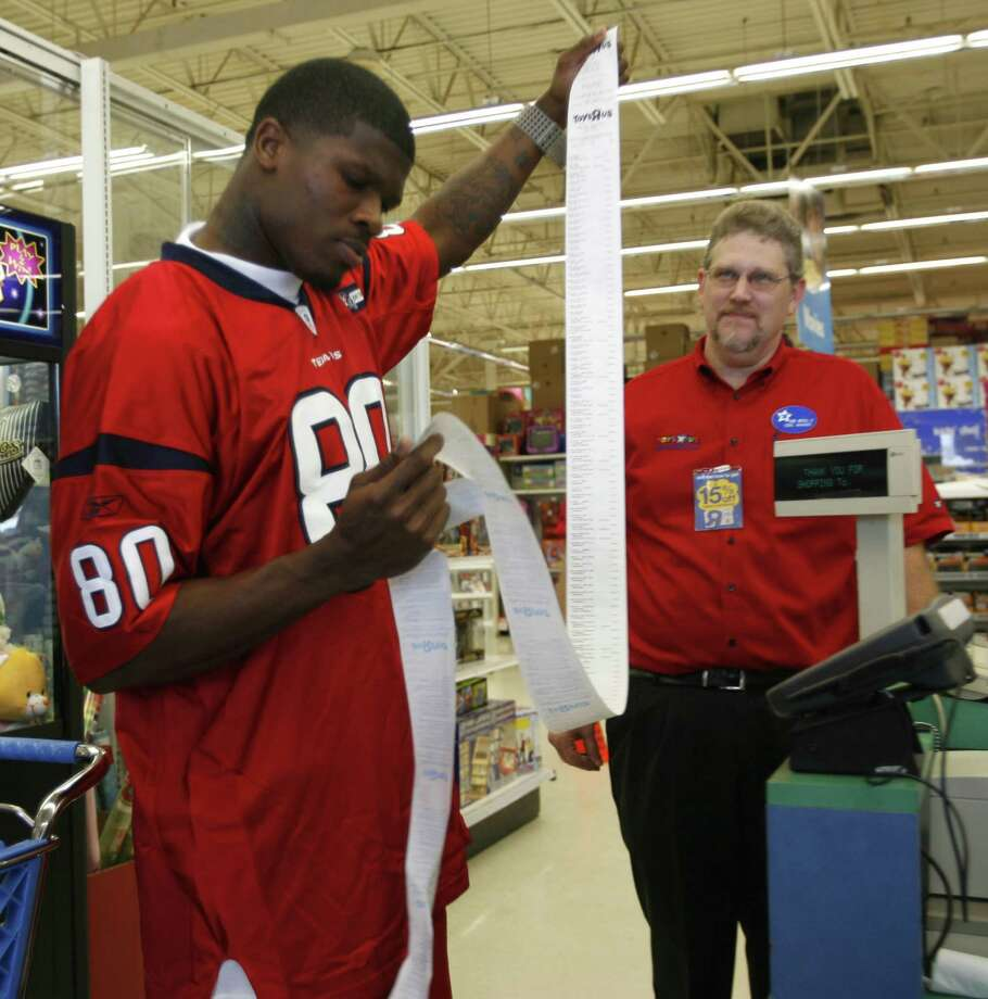 Houston Texans Andre Johnson checks his register tape after checking out (with Dave Mitchell, store manager) at Toys R Us on Old Spanish Trail and Kirby, where twelve kids were given 80 seconds to shop courtesy of Johnson, Monday December 18, 2007. Photo: Karen Warren, Houston Chronicle / © 2007 Houston Chronicle