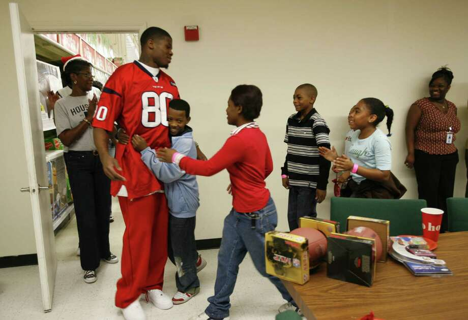 Andre Johnson gets surrounded by children wanting to hug him and thank him at Toys R Us on Old Spanish Trail and Kirby, where twelve kids were given 80 seconds to shop courtesy of  Houston Texans player Johnson, Monday December 18, 2007. Photo: Karen Warren, Chronicle / © 2007 Houston Chronicle
