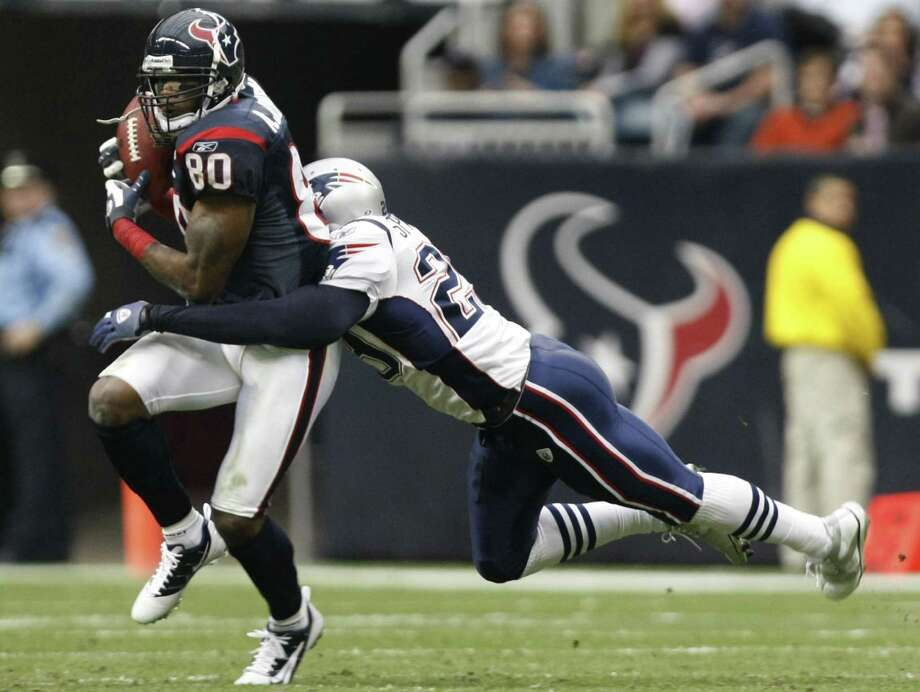 Houston Texans wide receiver Andre Johnson (80) is wrapped up by New England Patriots cornerback Darius Butler (28) during the third quarter of an NFL football game at Reliant Stadium on Sunday, Jan. 3, 2010, in Houston. Photo: Nick De La Torre, Houston Chronicle / © 2010 Houston Chronicle