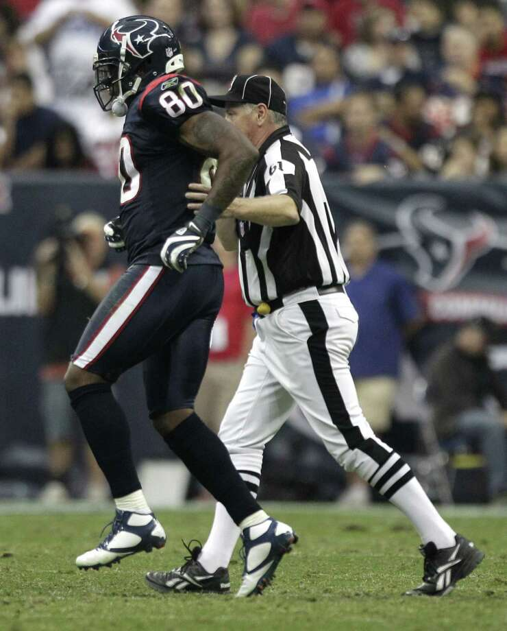 Texans wide receiver Andre Johnson (80) hops off the field past back judge Keith Ferguson (61) after suffering a leg injury during the third quarter. Photo: Brett Coomer, Houston Chronicle / © 2011  Houston Chronicle