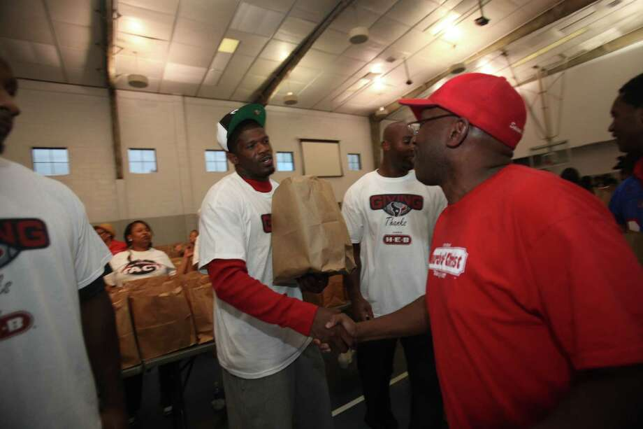 Texans Andre Johnson, DeMeco Ryans, Mario Williams, Antonio Smith, Brian Cushing and Johnathan Joseph hand out Thanksgiving meals to families from Houston's Fifth Ward community at the Fifth Ward Church of Christ on Tuesday, Nov. 22, 2011, in Houston. Texans players purchased 2,000 turkeys and groceries for families in the Fifth Ward. Photo: Mayra Beltran, Houston Chronicle / © 2011 Houston Chronicle