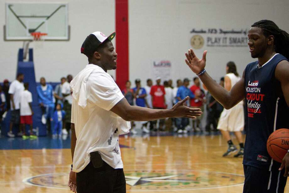 Texans wide receiver Andre Johnson shakes hands with Kenneth Faried of the Denver Nuggets while the teams warm up before the Houston Lockout Celebrity Basketball Game game at Delmar Fieldhouse on Sunday, Nov. 20, 2011, in Houston. Johnson watched from the bench as he sat with the NBA players during the game. Photo: Smiley N. Pool, Houston Chronicle / © 2011  Houston Chronicle