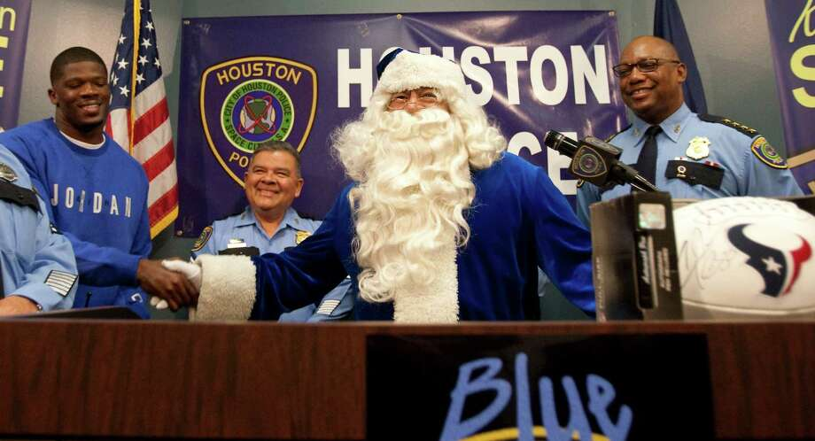 Texans wide receiver Andre Johnson, left, shakes hands with Blue Santa, portrayed by HPD senior officer David Morales, during a press conference to kick off the Blue Santa Christmas Campaign Tuesday, Nov. 29, 2011, at the Houston Police Department's headquarters in Houston. Photo: Nick De La Torre, Houston Chronicle / © 2011  Houston Chronicle