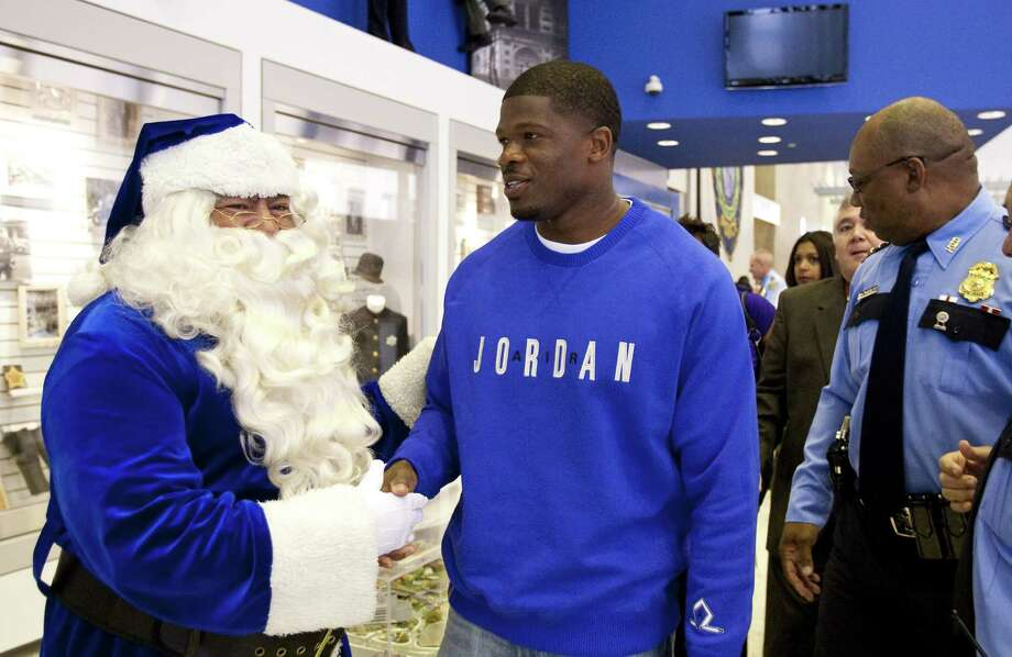 HPD senior officer David Morales, posing as Blue Santa, meets Houston Texans wide receiver Andre Johnson before a press conference to kick off the Blue Santa Christmas Campaign Tuesday, Nov. 29, 2011, at the Houston Police Department's headquarters in Houston. Photo: Nick De La Torre, Houston Chronicle / © 2011  Houston Chronicle
