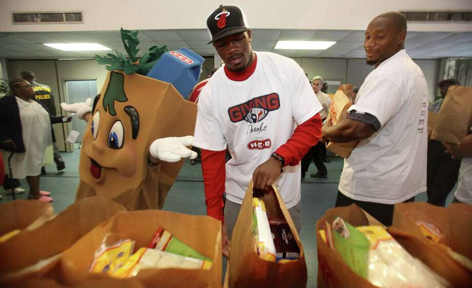 Texans Andre Johnson and Antonio Smith replenish the grocery bags while they hand out Thanksgiving meals to families from Houston's Fifth Ward community at the Fifth Ward Church of Christ on Tuesday, Nov. 22, 2011, in Houston. The Texans players purchased 2,000 turkeys and groceries for families in the Fifth Ward. Photo: Mayra Beltran, Houston Chronicle / © 2011 Houston Chronicle