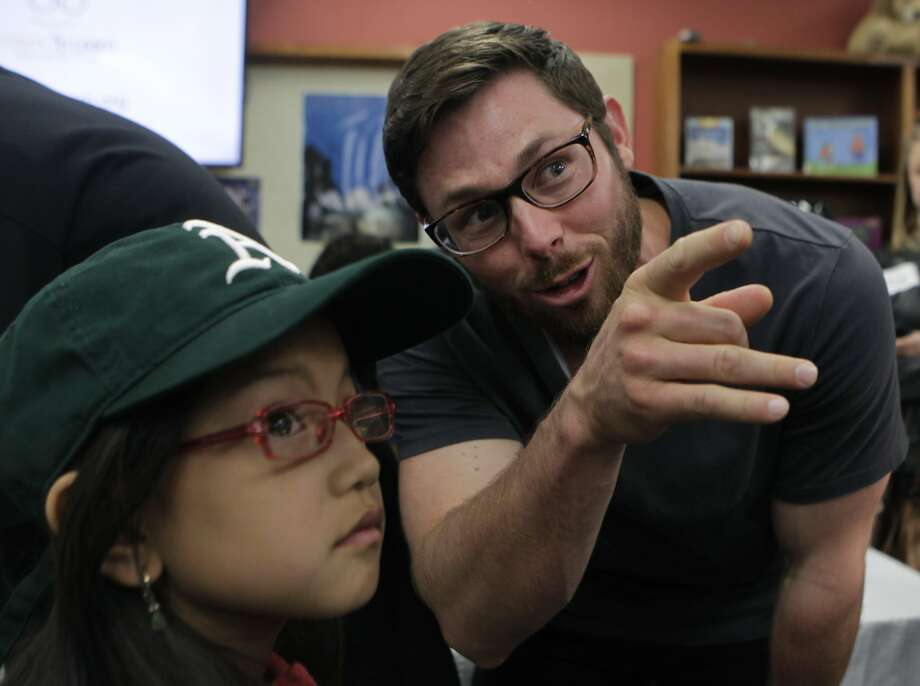 A's infielder Eric Sogard checks to see if Minh Nguyen's free eyeglasses fit at Franklin Elementary. Photo: Paul Chinn, The Chronicle