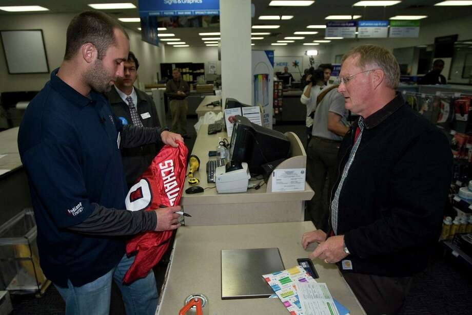 "Texans quarterback Matt Schaub (left) autographs a jersery being shipped by Keith Landsness (right) during the FedEx Office ""Pack and Ship"" promotion at the FedEx Office location at 2200 Southwest Freeway Tuesday, Dec. 1, 2009, in Houston Photo: James Nielsen, Houston Chronicle / Houston Chronicle"
