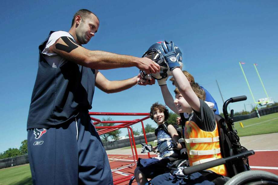 Texans quarterback Matt Schaub allows Aaron Berry, 8, to try on his helmet as brother (center) Peter Berry, 9, looks on at the Houston Texans Practice Facility on Wednesday, Oct. 19, 2011, in Houston.    Peter Berry, 9, Aaron Berry, 8, not present Willa Berry, 6, are the children whose parents died in a head-on collision earlier this year, and the children are now paralyzed. The Berry brothers and family meet Texans players after practice. Photo: Mayra Beltran, Houston Chronicle / © 2011 Houston Chronicle