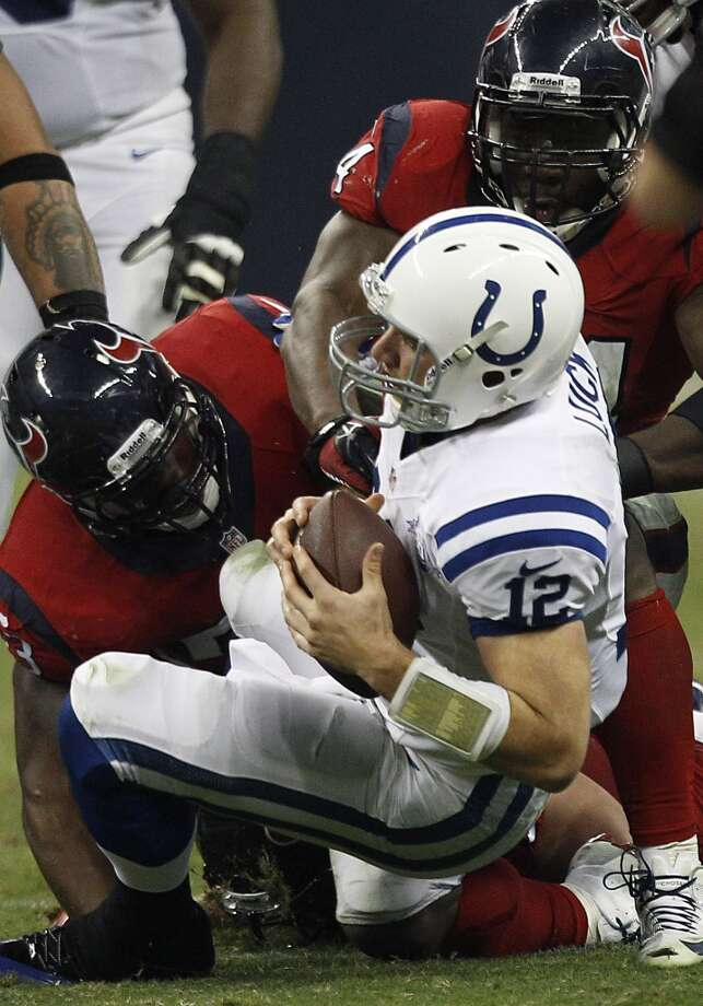 Colts quarterback Andrew Luck (12) is brought down by Texans inside linebacker Joe Mays (53) and defensive end Antonio Smith (94) on Sunday, Nov. 3, 2013. Photo: Brett Coomer, Houston Chronicle