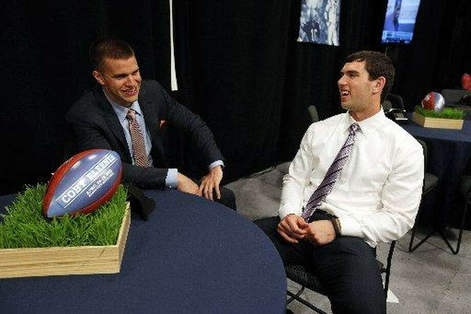 Andrew Luck awaits the call with Stanford teammate Coby Fleener. Photo: Jason DeCrow, AP